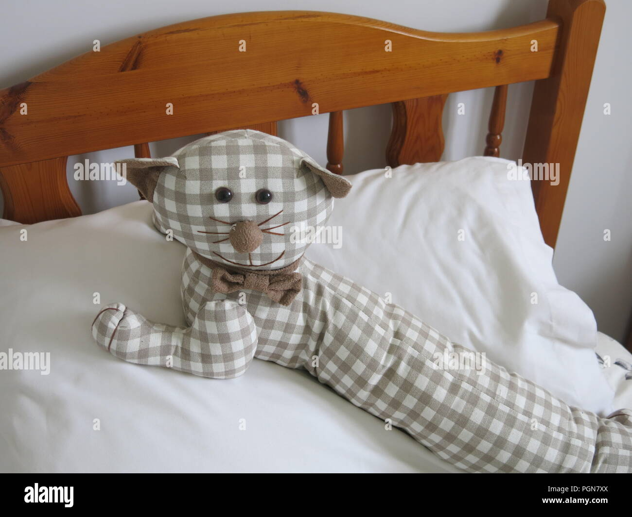 This Toy Stuffed Cat Made From Gingham Fabric Is Reclining On The
