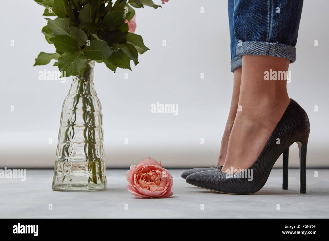 92a332cfbfa On the floor is one pink rose, a glass vase with green branches near the  legs of a girl shod with black shoes on high heels on a gray background