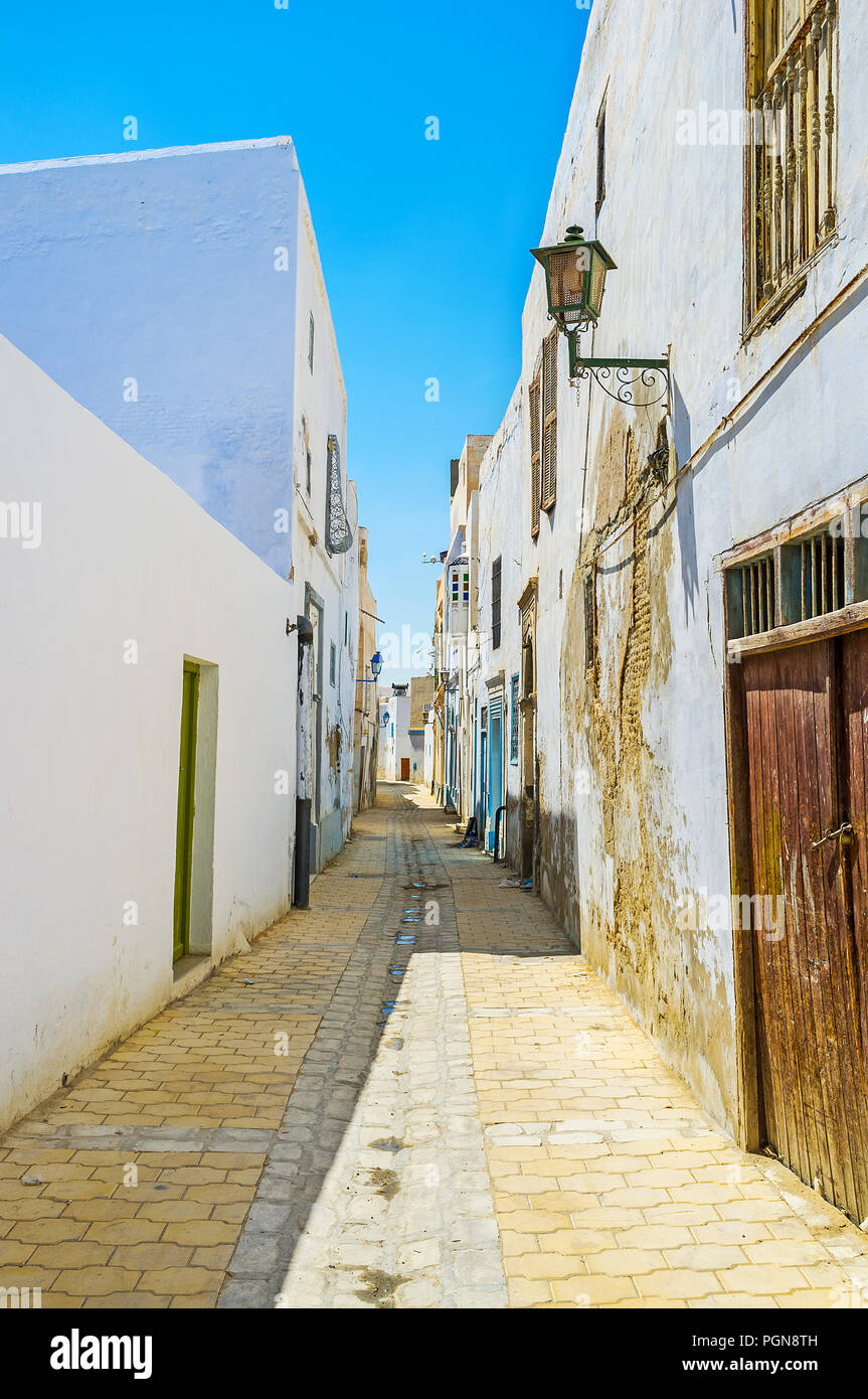 The authentic houses along the narrow street of Medina with traditional white blank walls, also serving as the fencies, hiding the inner yards, Kairou - Stock Image
