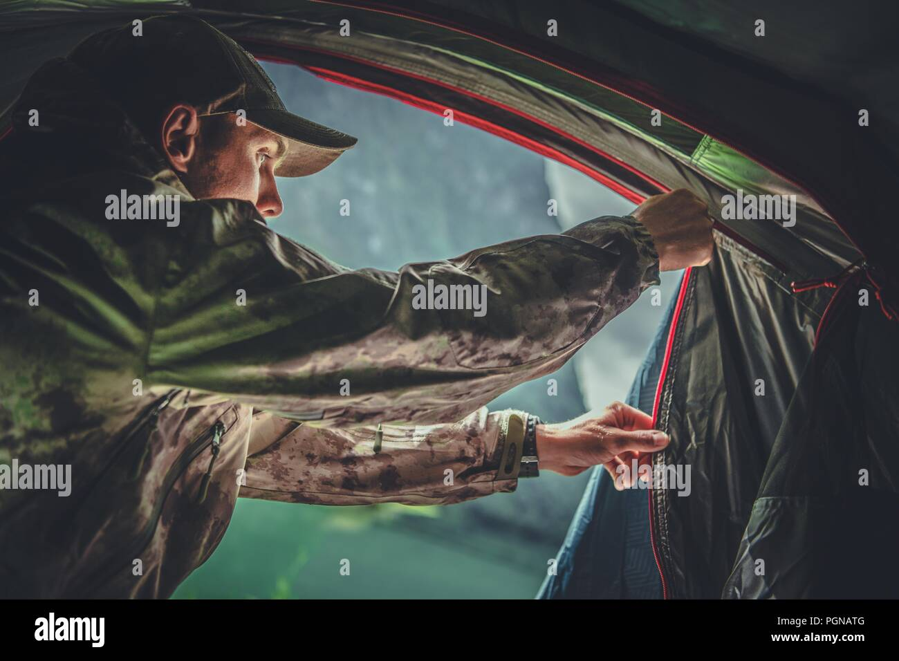 Game Hunter Camping Spot. Caucasian Hunting Men in His 30s Closing His Tent From Inside. - Stock Image