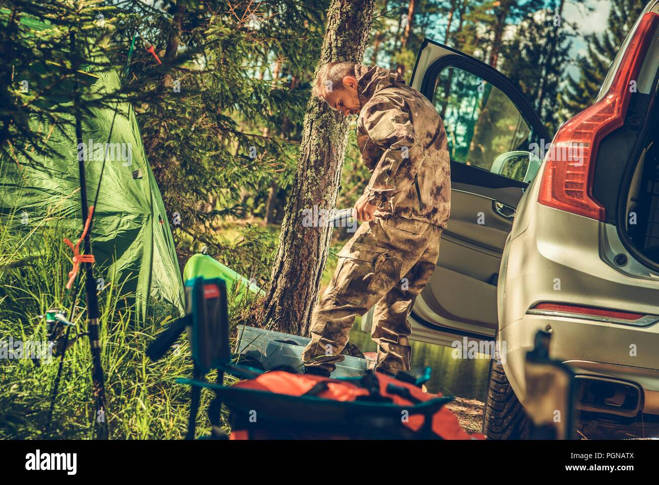 Hunting Season is On. Caucasian Hunter Setup His Camp and the Gear. - Stock Image