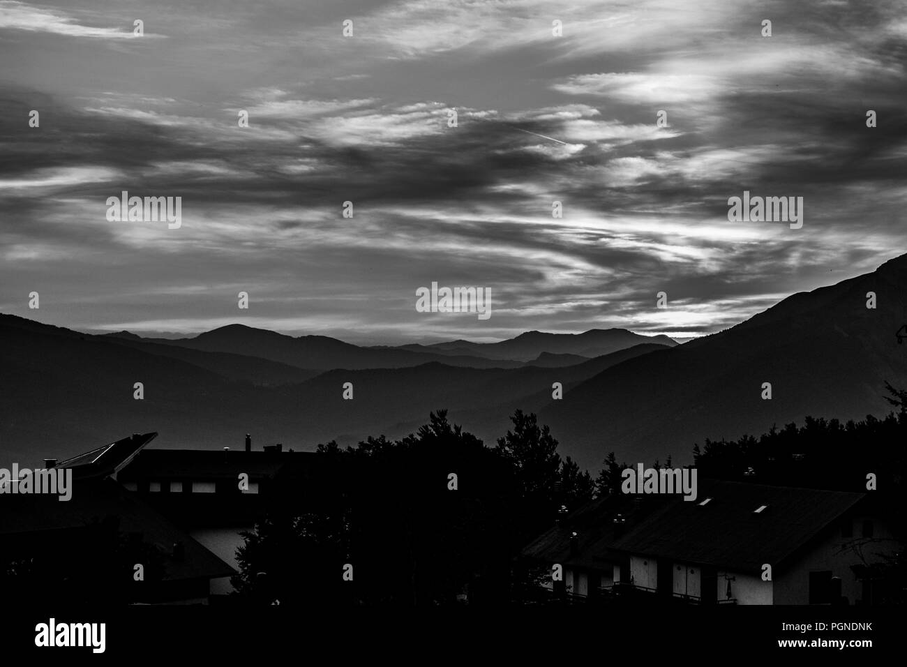 Profile of mountain and city with cloudy sky in black and white Stock Photo