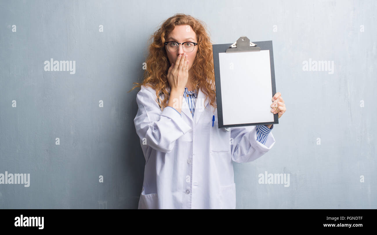 young redhead doctor woman over grey grunge wall showing clipboard
