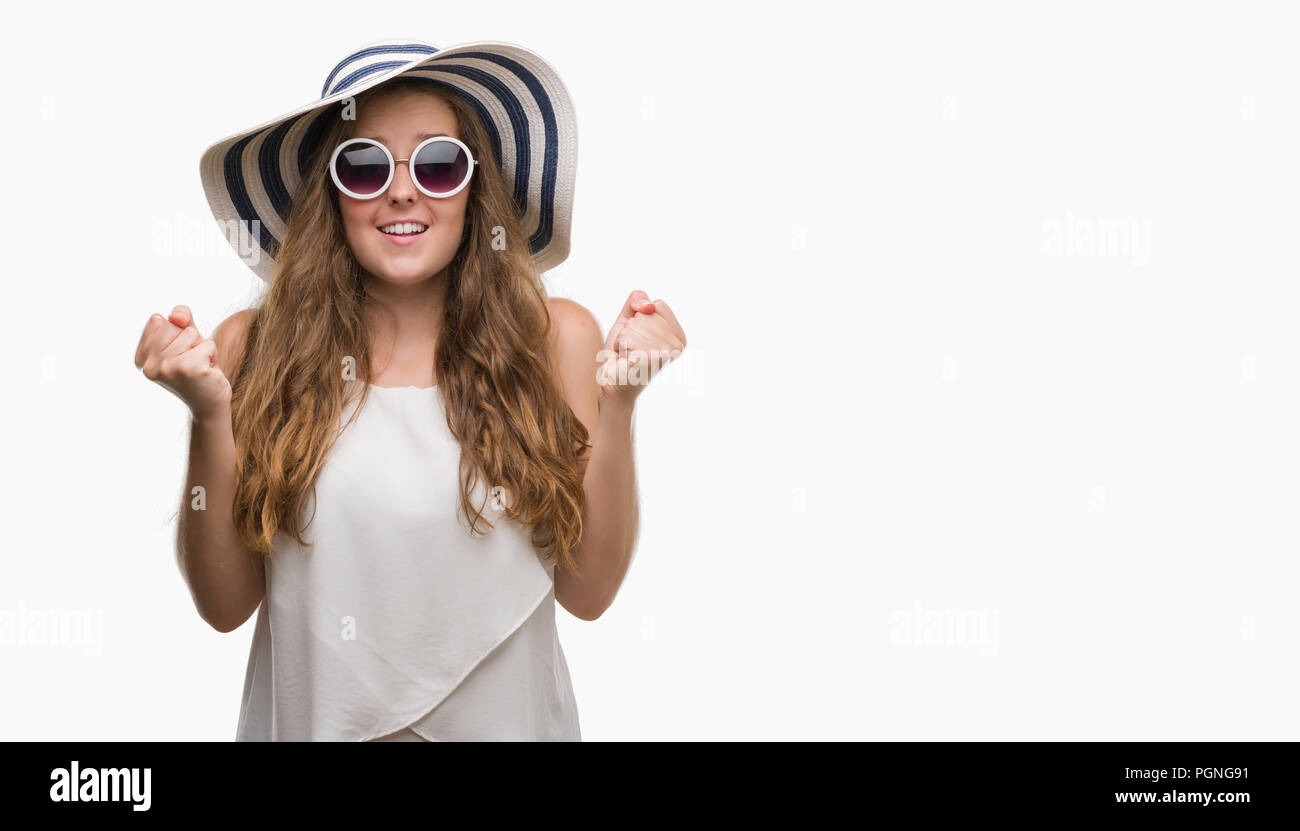 Young blonde woman wearing sunglasses and summer hat screaming proud and celebrating victory and success very excited, cheering emotion - Stock Image