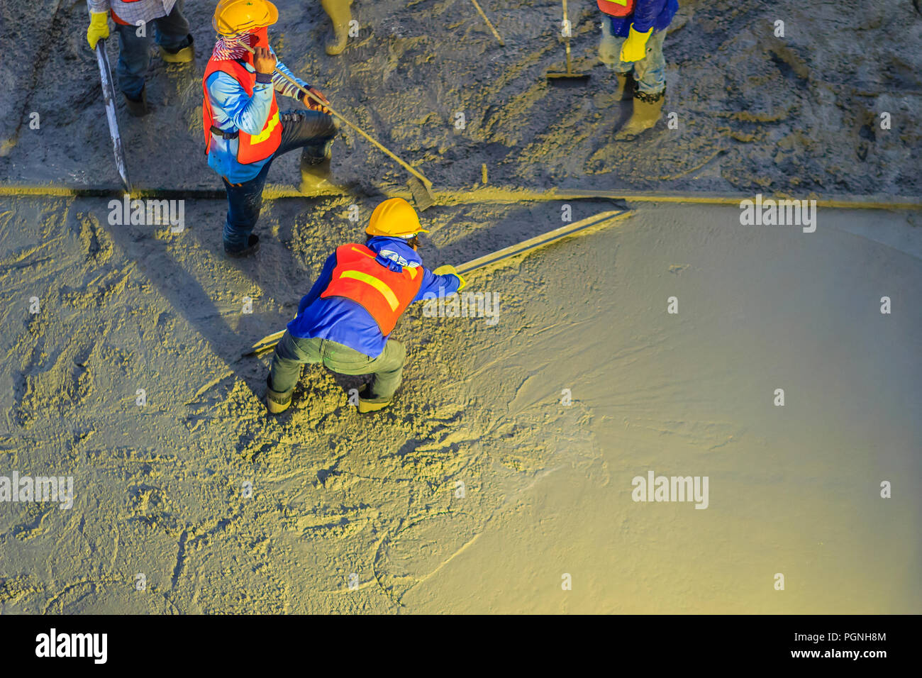 Mason worker leveling concrete with trowels, mason hands spreading poured concrete. Concreting workers are leveling poured liquid concrete on a steel  Stock Photo