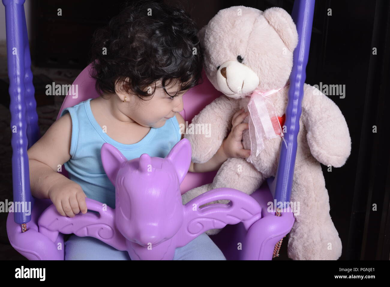 Portrait of a little baby girl on unicorn swing with jealousy act to teddy bear doll - Stock Image