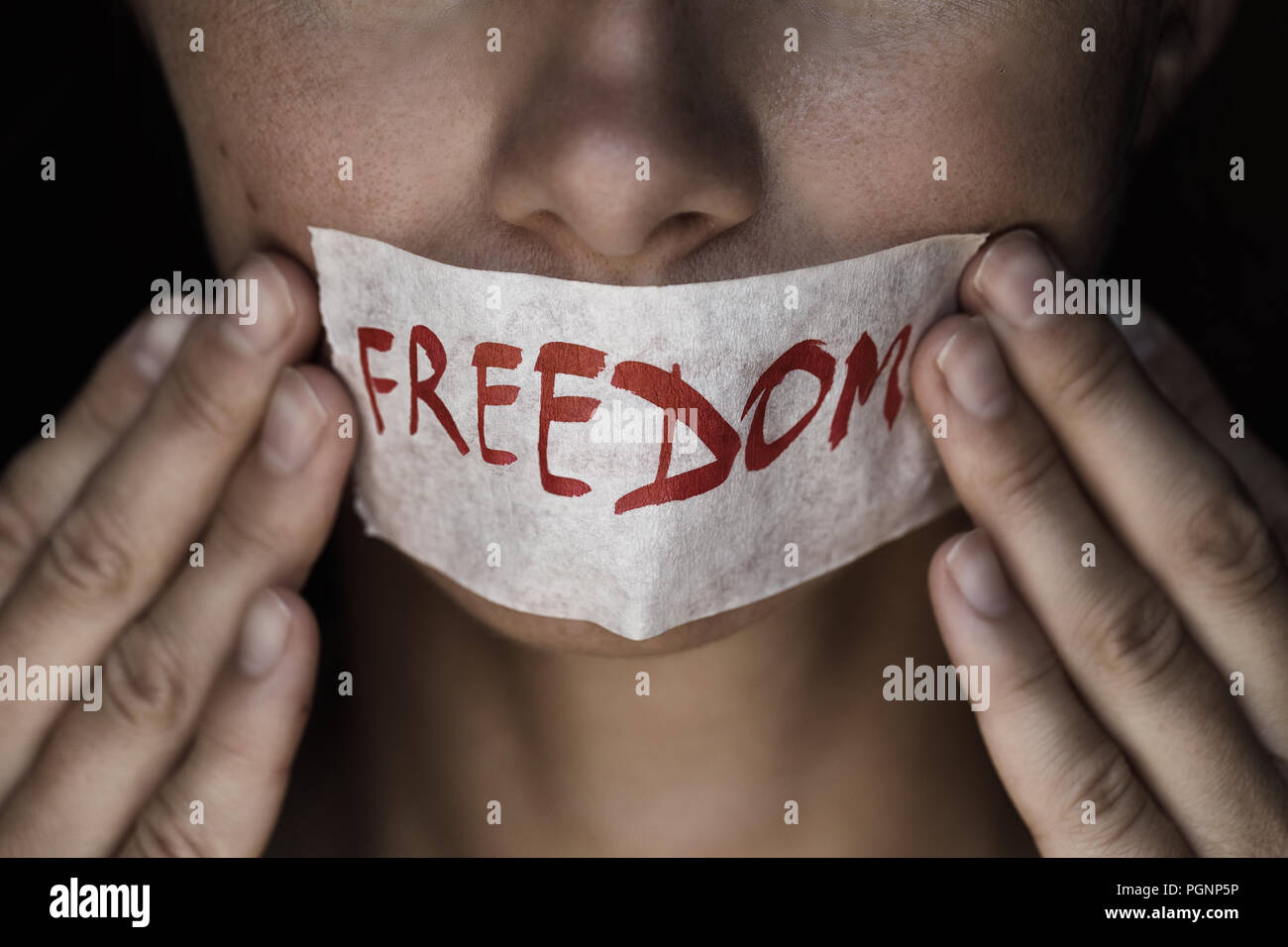 Concept on the topic of freedom of speech: the girl's face is sealed with scotch tape - Stock Image