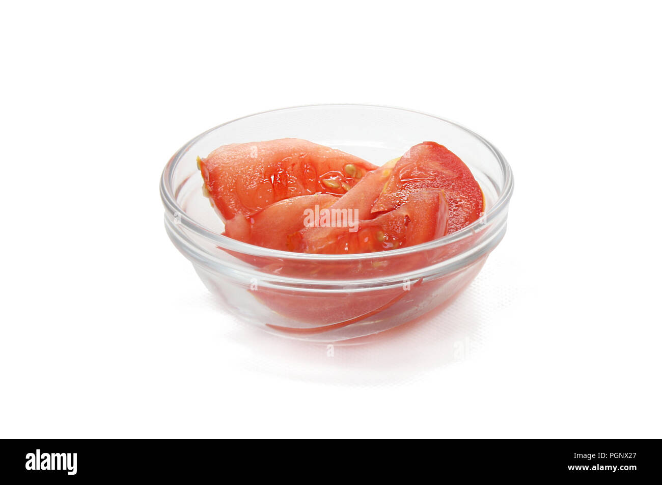 Slices of tomato in glass bow isolated on real studio white background Stock Photo