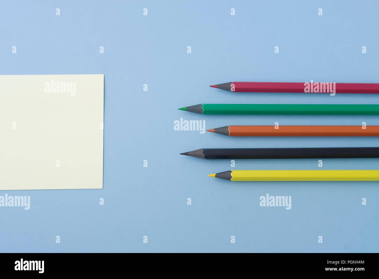 Note with multicolored pencils aligned at the center of the photo isolated on light blue, pastel table. Space for additional text in flat lay style fo Stock Photo