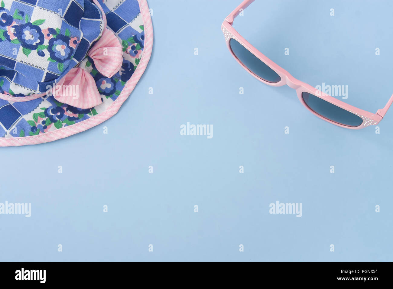 Colorful hat and pink sunglasses isolated on light blue pastel background. Space for text. Flat lay style. Stock Photo