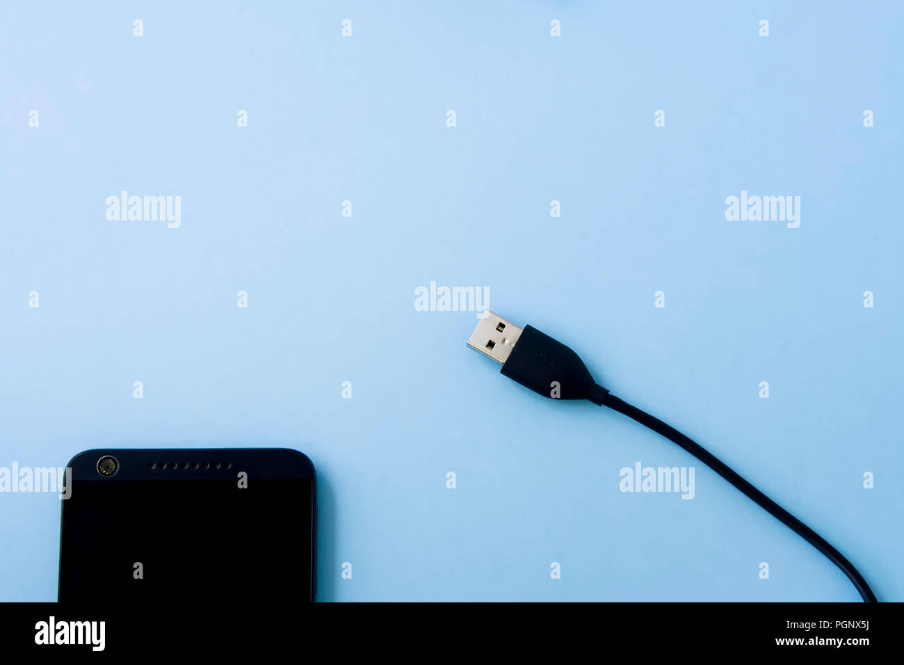 USB plug with mobile phone isolated on light pastel blue background desk, table in flat lay style. Space for text. Stock Photo