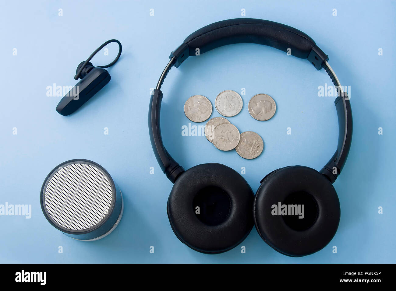 Coins, wireless headset, headphones and speaker on blue pastel isolated desk. Flat lay. Stock Photo