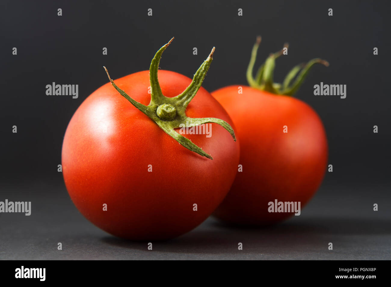 Group of tomatoes isolated on black with leaf and stem. There are around 7,500 tomato varieties grown for various purposes.Tomato varieties can be div Stock Photo