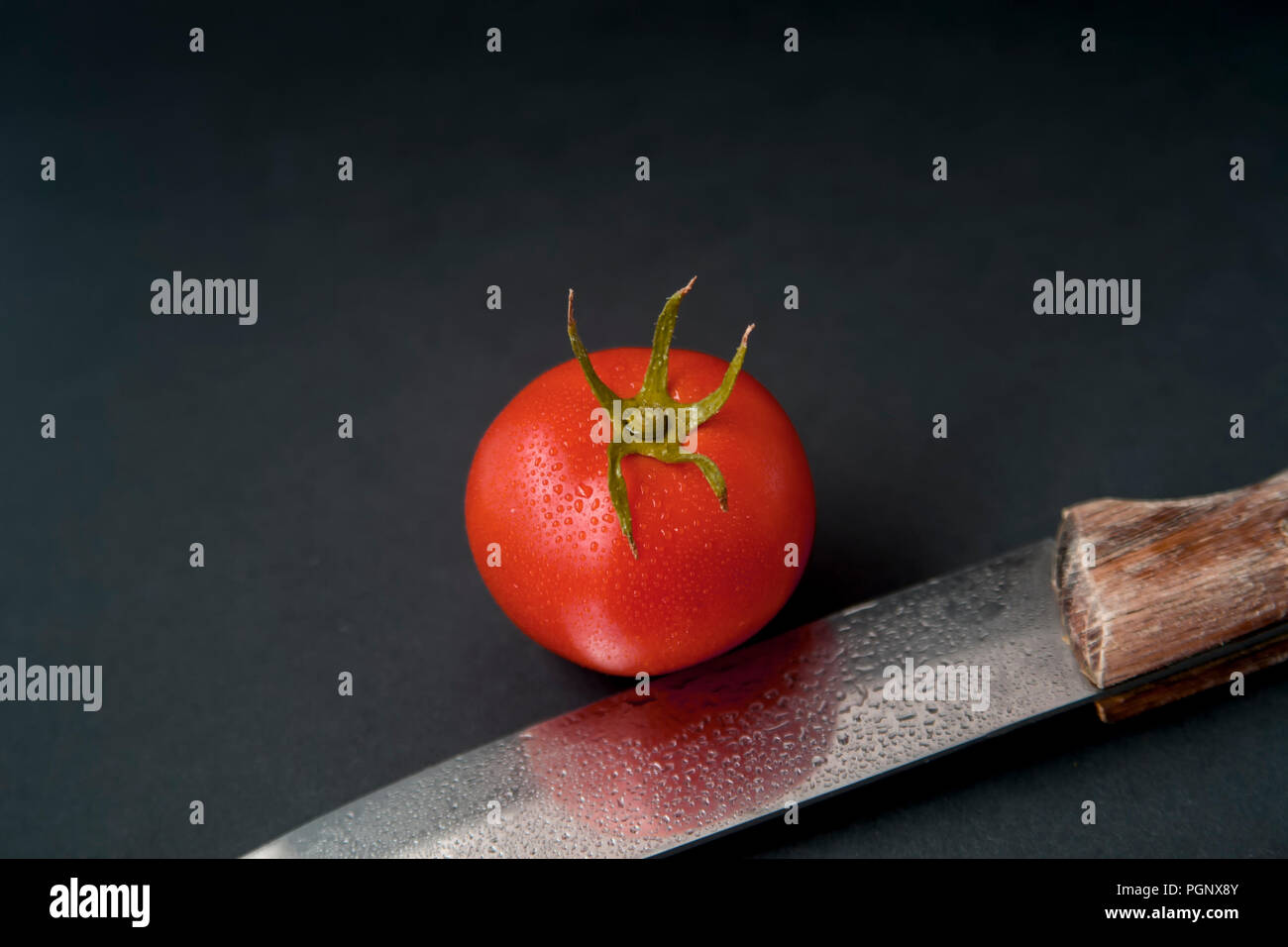 Single tomato isolated on black with stem, leaf. Top view. Knife with water droplets in front of the tomato showing reflection. Tomato cultivars vary  Stock Photo