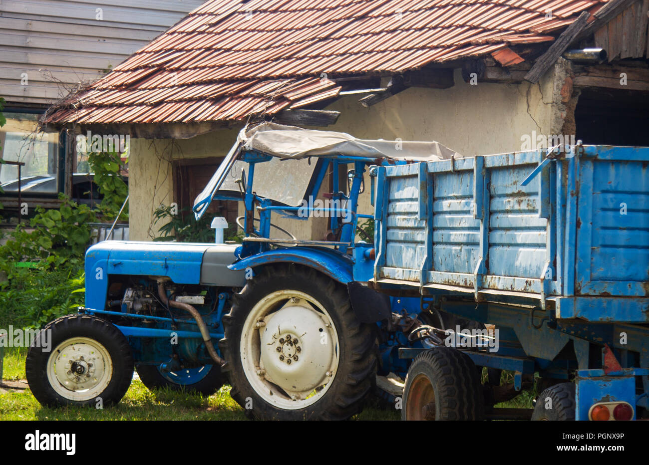 Blue tractor parking at the courtyard of the old, aged house. Ready to work. Stock Photo