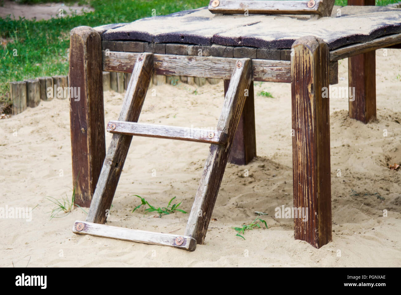 Aged, worn wooden ladder at the playground in the sandbox. Stock Photo