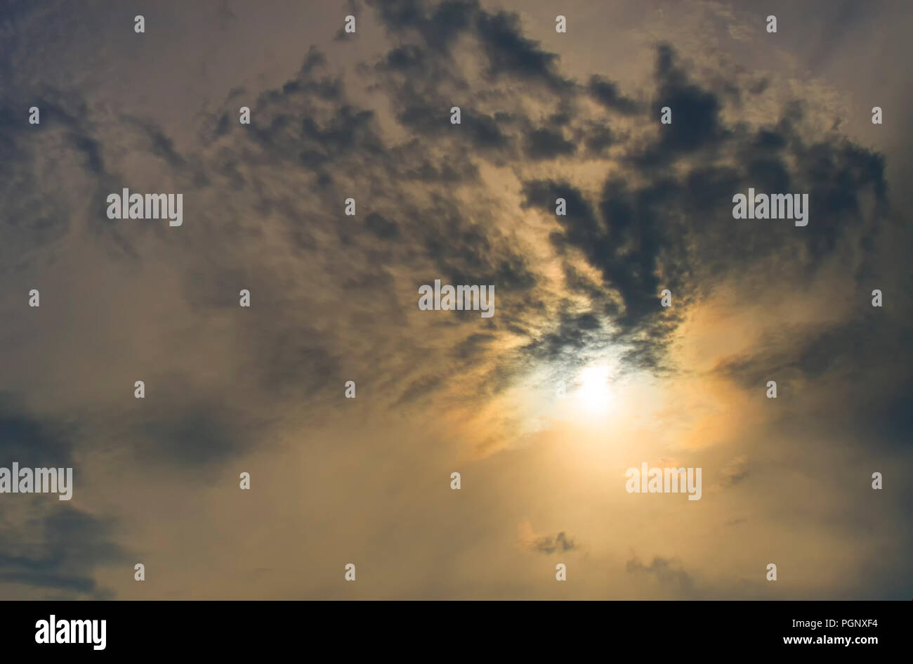 Sun rising behind the dark clouds, dark orange tone. Stock Photo