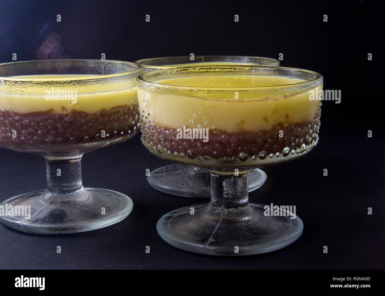Mousse, souffle, pudding with vanilla and chocolate in glass black, dark background. Stock Photo