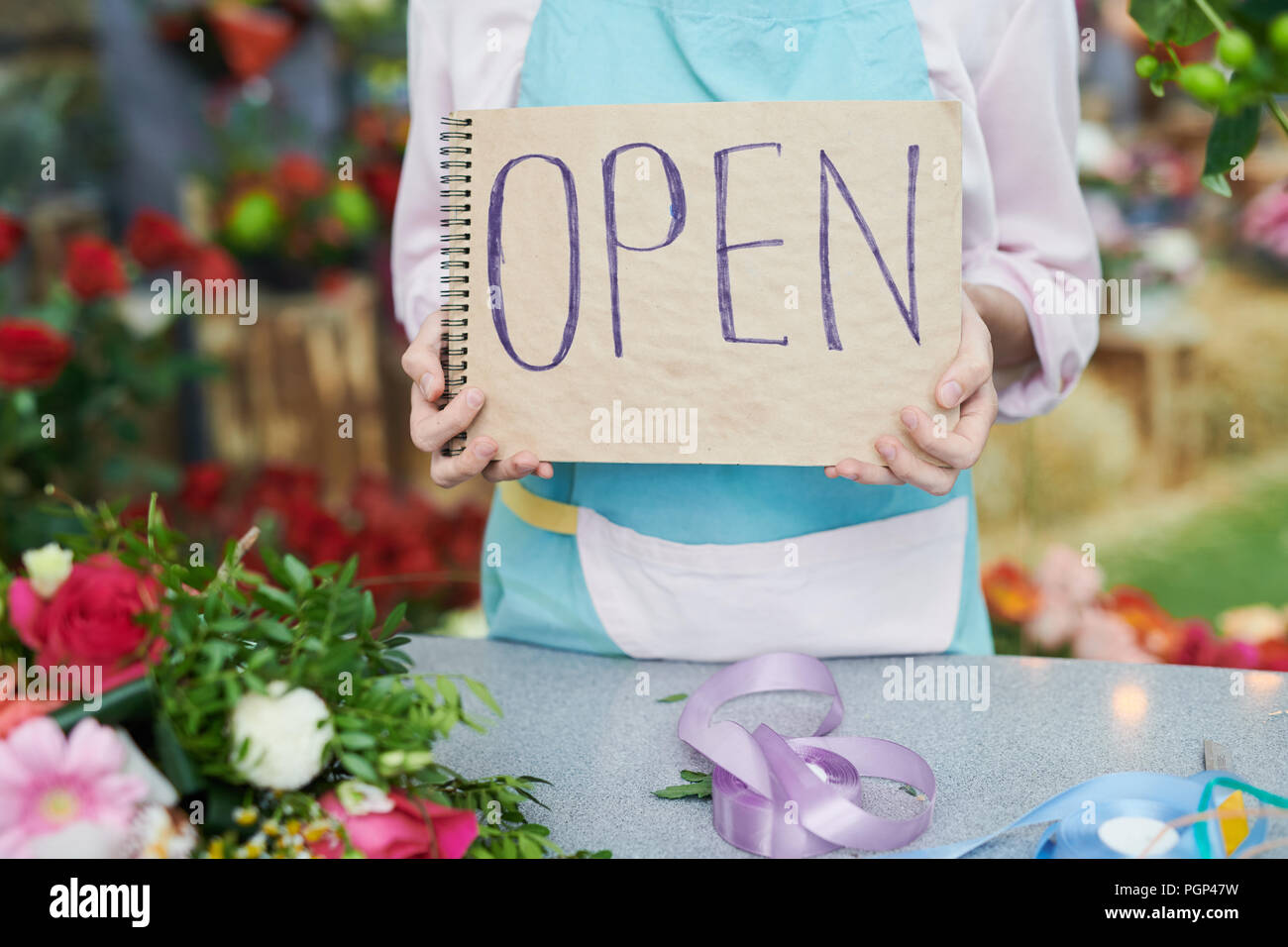 Closeup of unrecognizable florinst holding sign with word OPEN Stock Photo