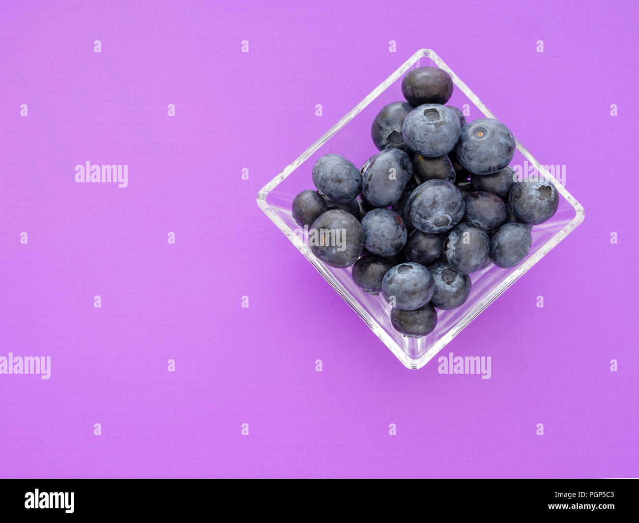 Healthy superfood blueberries in square glass bowl on beautiful purple background. With copyspace. - Stock Image