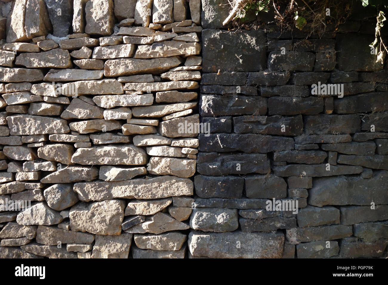 Very New dry stone wall next to a very Old Dry stoned dark stone wall joined up shows wonderful contrasting two walls - Stock Image