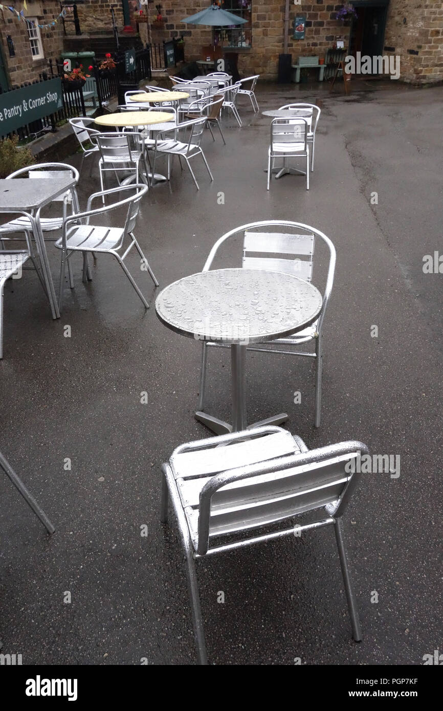 Empty courtyard cafe seating in the english rain - Stock Image