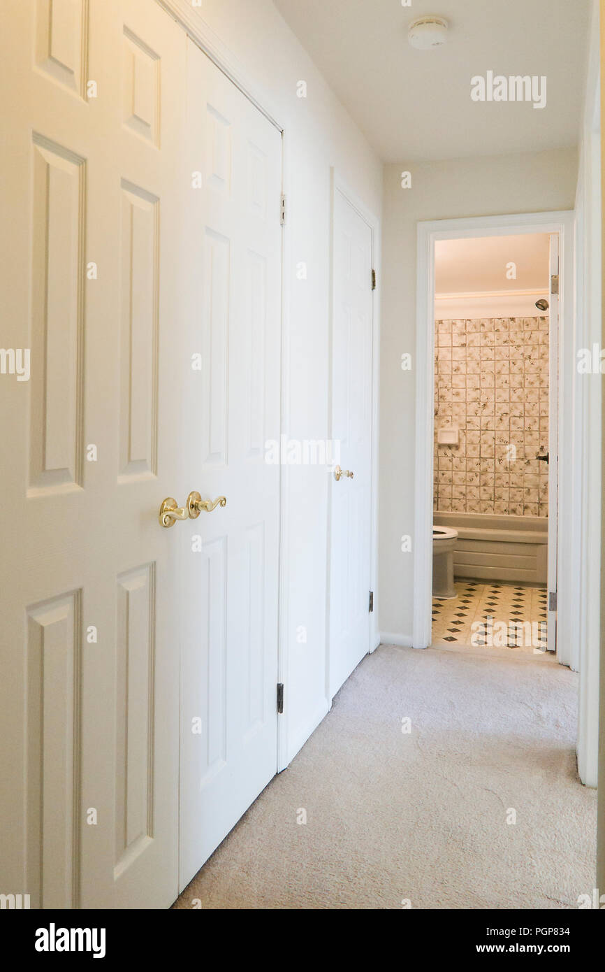 Hallway leading to bathroom of small condominium unit painted in white - USA - Stock Image