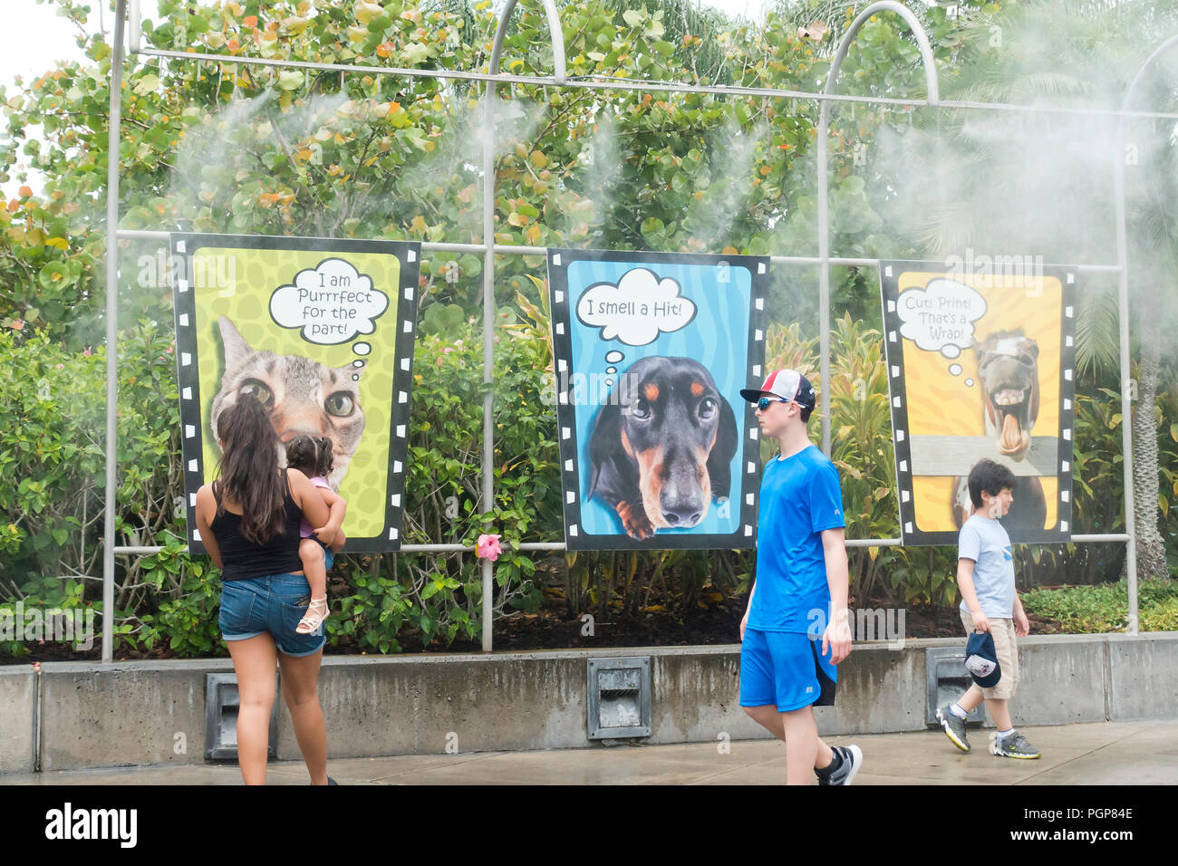 People walking under misting system (mist cooling system) at a theme park - USA - Stock Image