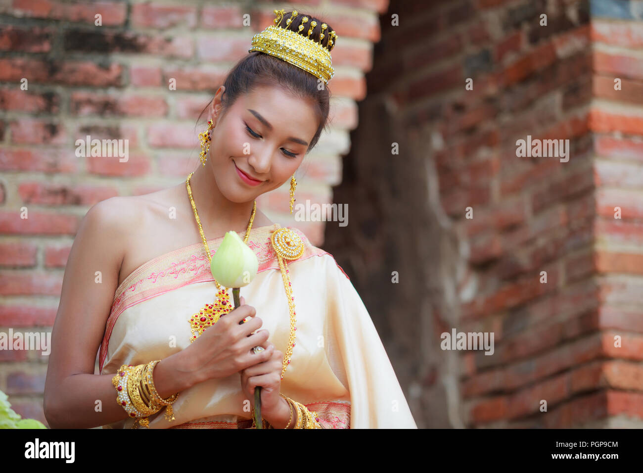 woman in traditional clothes fold lotus flower petals used in rituals of Buddhism religion. A Lotus represents purity of body, speech, and mind, float - Stock Image