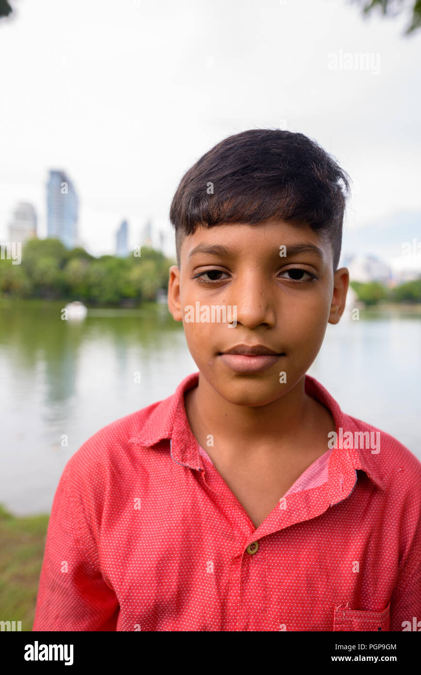 Portrait of young Indian boy relaxing at the park - Stock Image