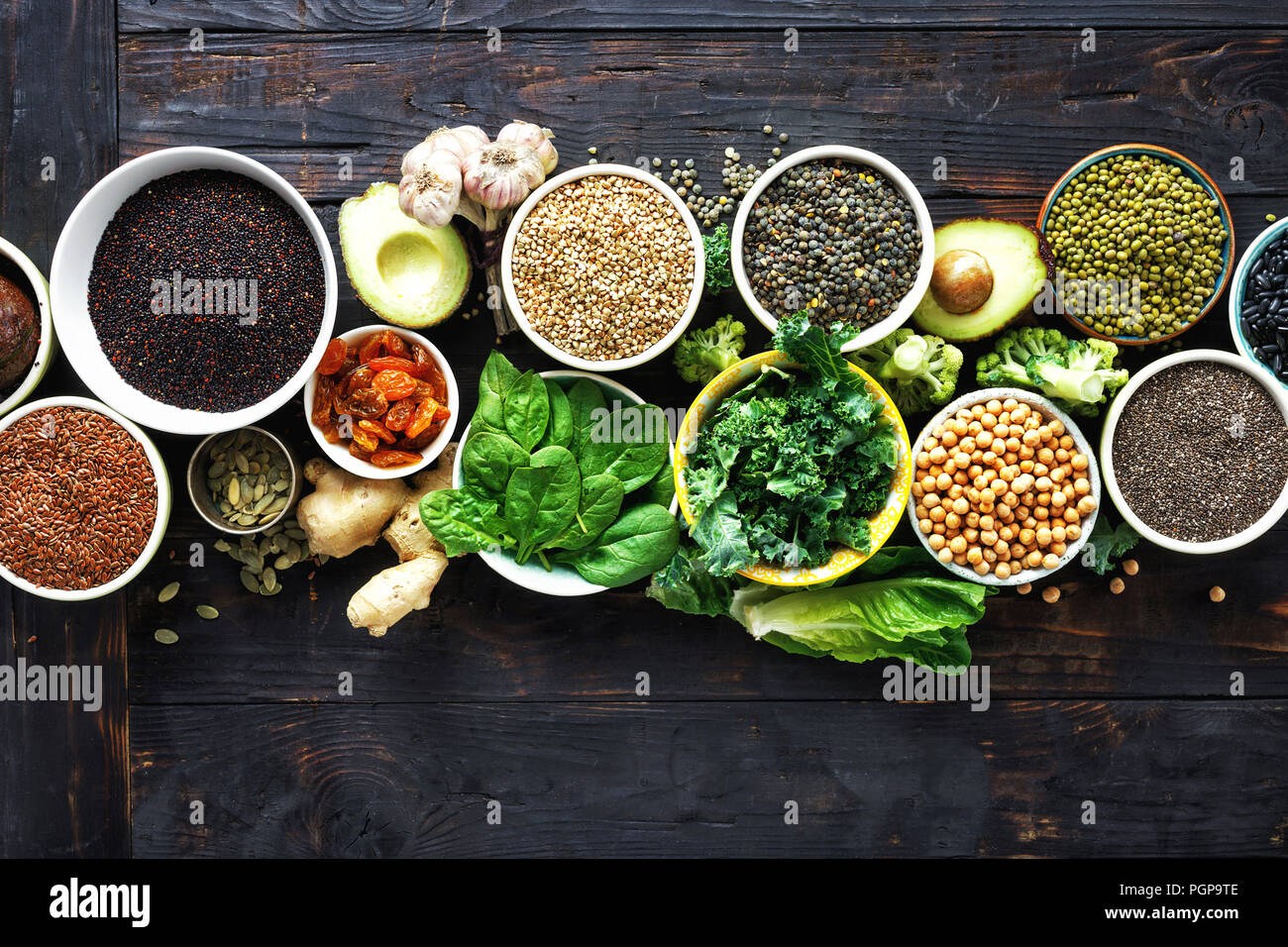 Vegetarian or diet food concept. Set raw seeds, cereals, beans, superfoods and green vegetables on dark wooden background top view - Stock Image