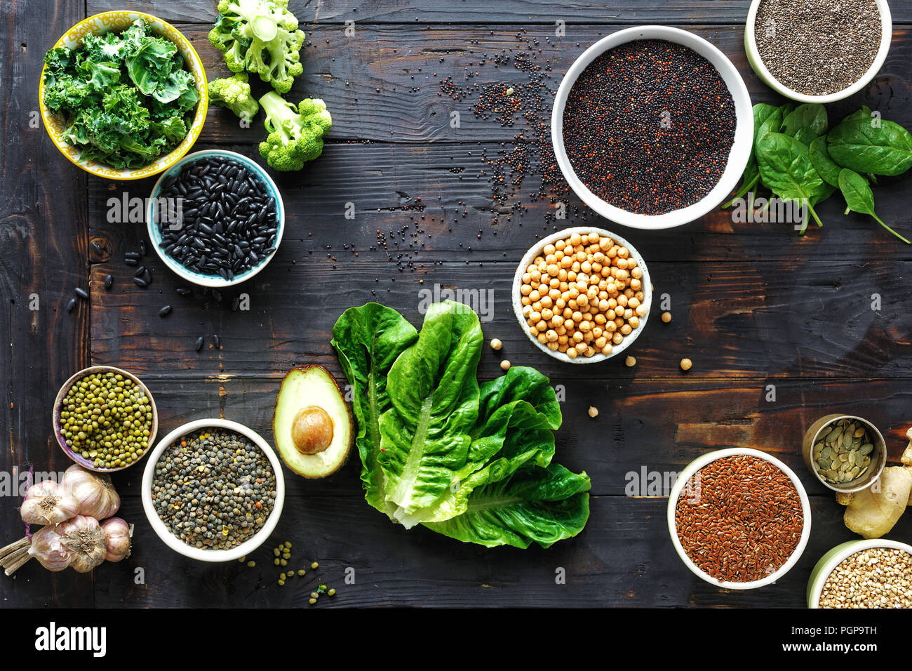 Raw seeds, cereals, beans, superfoods and green vegetables on dark wooden table top view. vegetarian or diet food concept - Stock Image