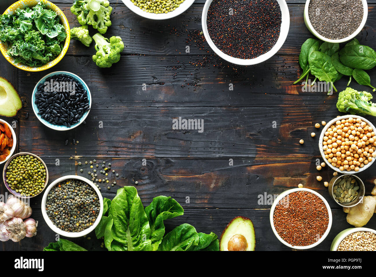 Frame of set raw seeds, cereals, beans, superfoods and green vegetables on dark wooden background top view. vegetarian or diet food concept - Stock Image