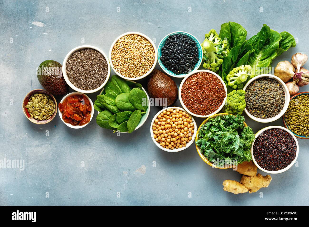 Vegetarian healthy food concept. Set raw seeds, cereals, beans, superfoods and green vegetables on blue stone background top view flat lay - Stock Image