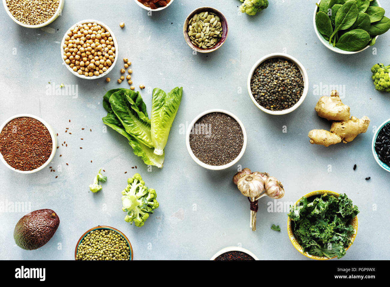 Set raw seeds, cereals, beans, superfoods and green vegetables on blue stone background top view. vegetarian or diet food concept - Stock Image