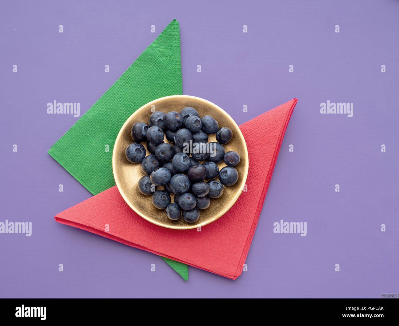 Healthy superfood blueberries on colourful background with paper napkins, serviettes and gold plate. - Stock Image