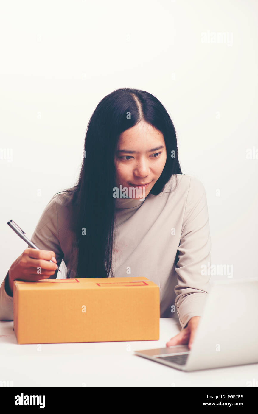 startup small business owner working with computer at workplace. freelance woman seller check product order, packing goods for delivery to customer. O Stock Photo