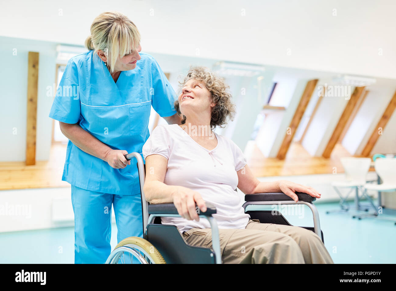Caring caregiver takes care of a senior woman in a wheelchair at rehab - Stock Image