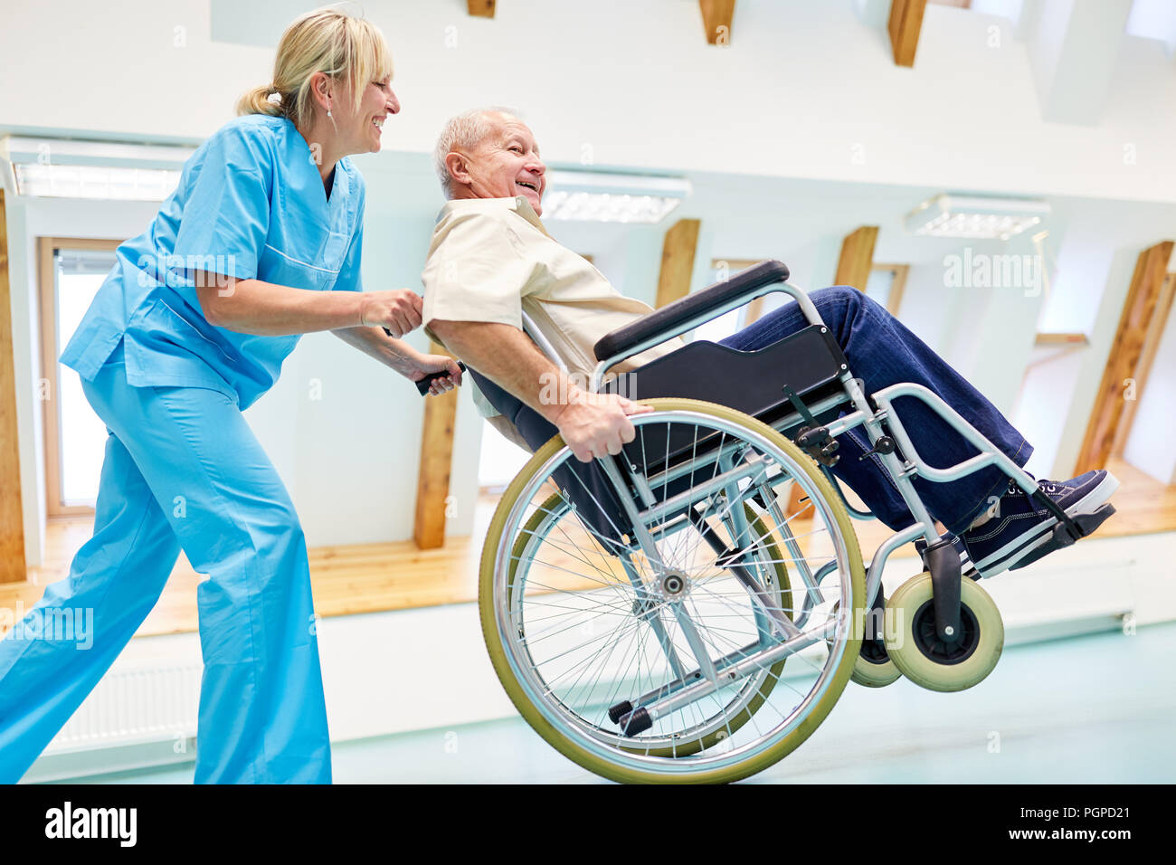 Caregiver and senior in a wheelchair silly around in retirement home or rehab - Stock Image