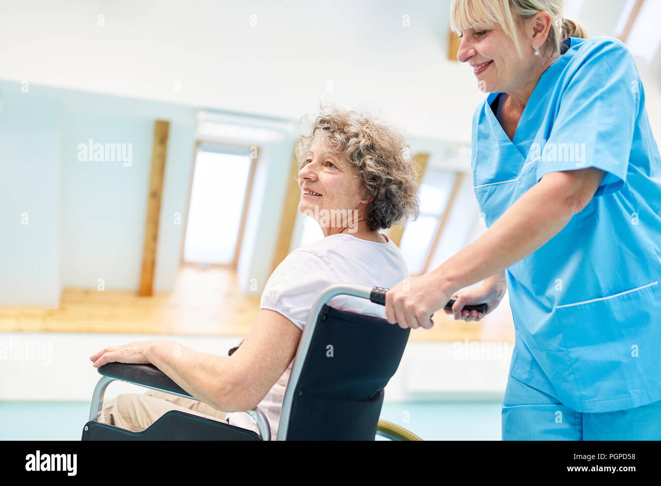 Caregiver cares for a senior woman in a wheelchair in physiotherapy - Stock Image