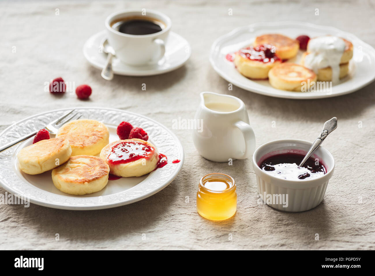 Breakfast Table With Curd Fritters or Pancakes, Coffee, Jam and Honey. Russian, Ukrainian cuisine. Cozy breakfast or comfort food concept - Stock Image