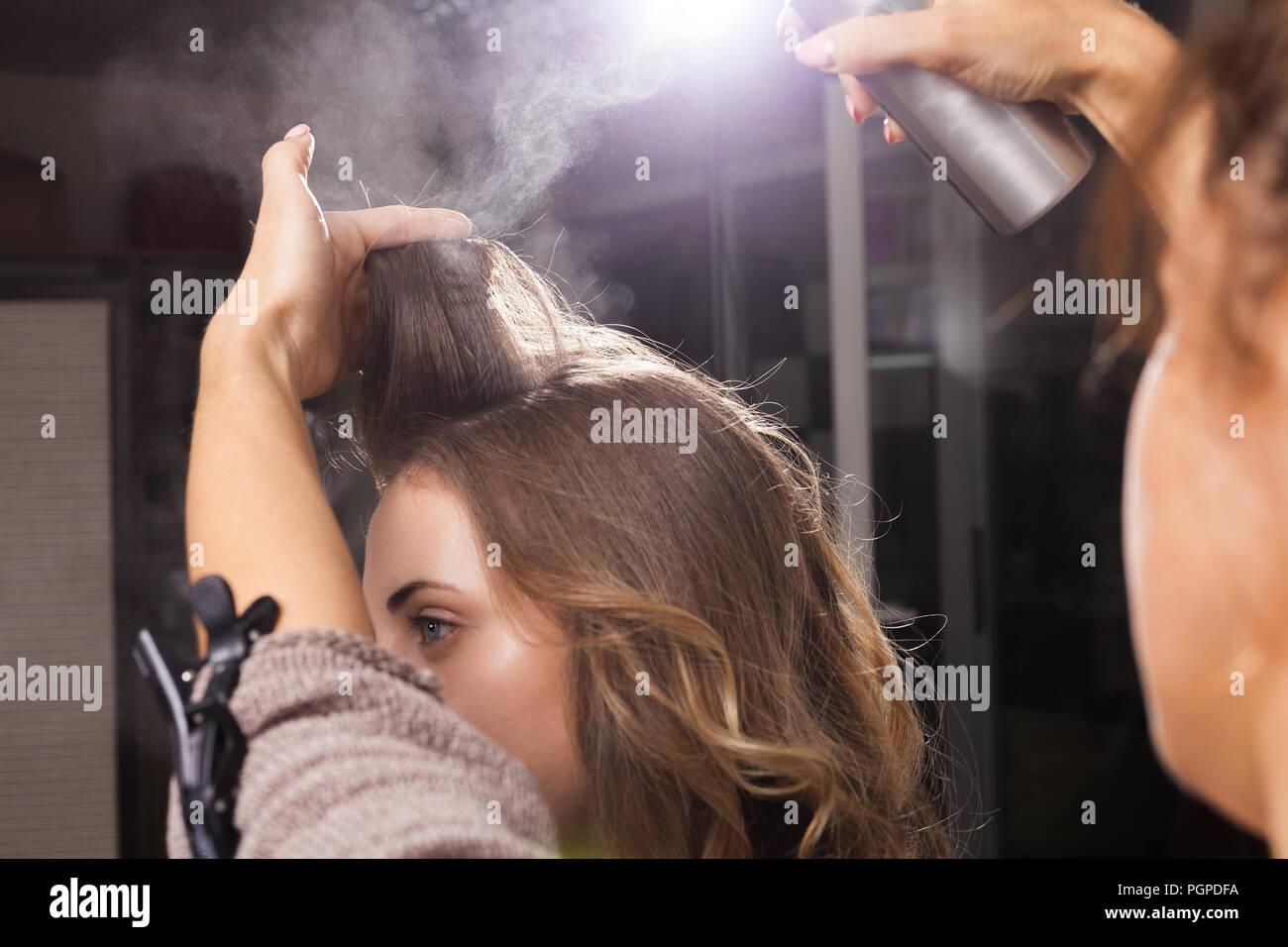 hairdresser fixing a coiffure of a girl with a hair spray - Stock Image