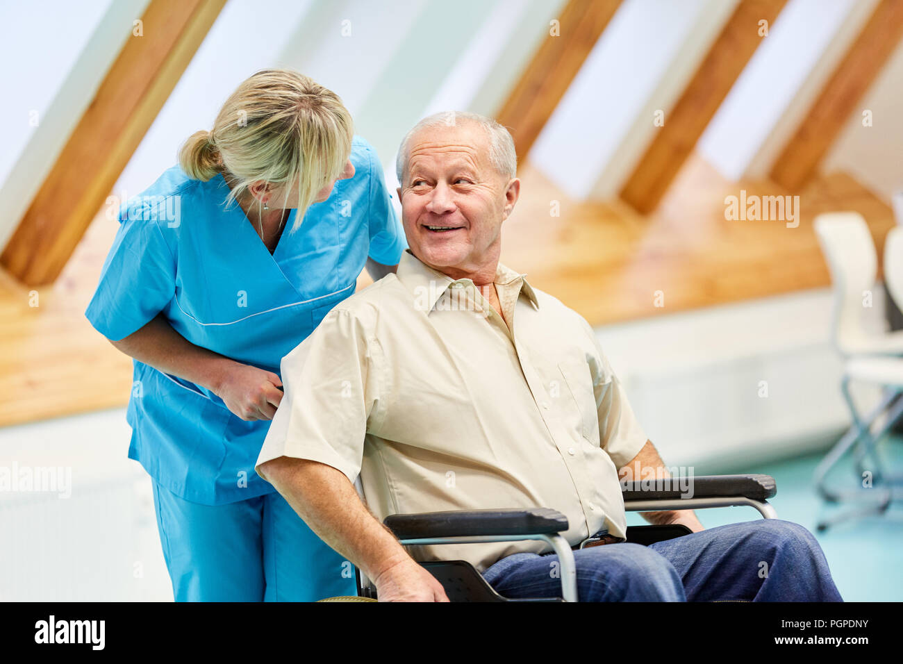 Senior man in wheelchair is happy about the caregiver in the elderly care - Stock Image