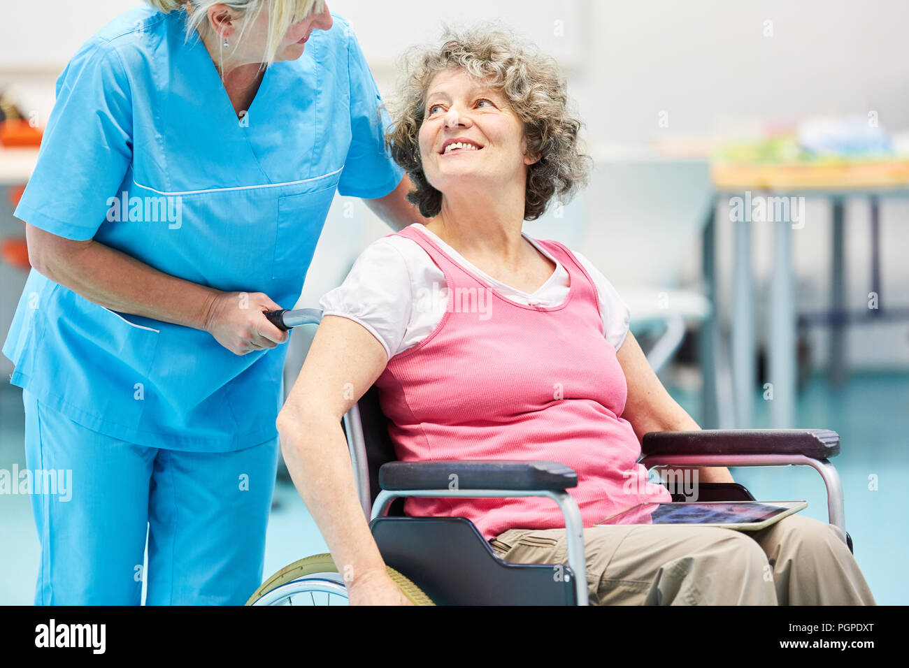 Nurse caring for senior woman in wheelchair after stroke in rehab clinic - Stock Image