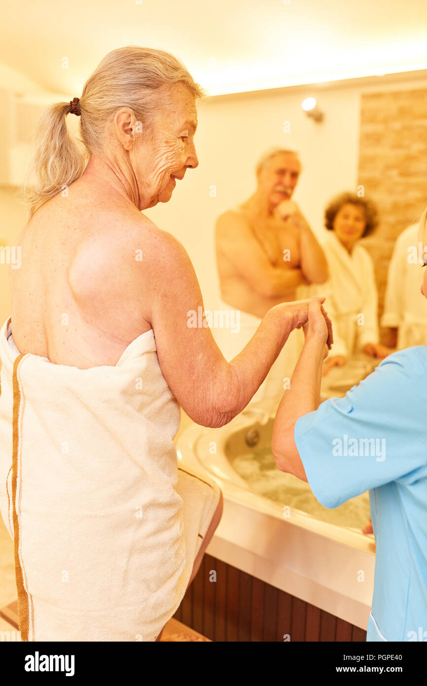 Caregiver helps senior woman in the spa spa while bathing in the hot ...