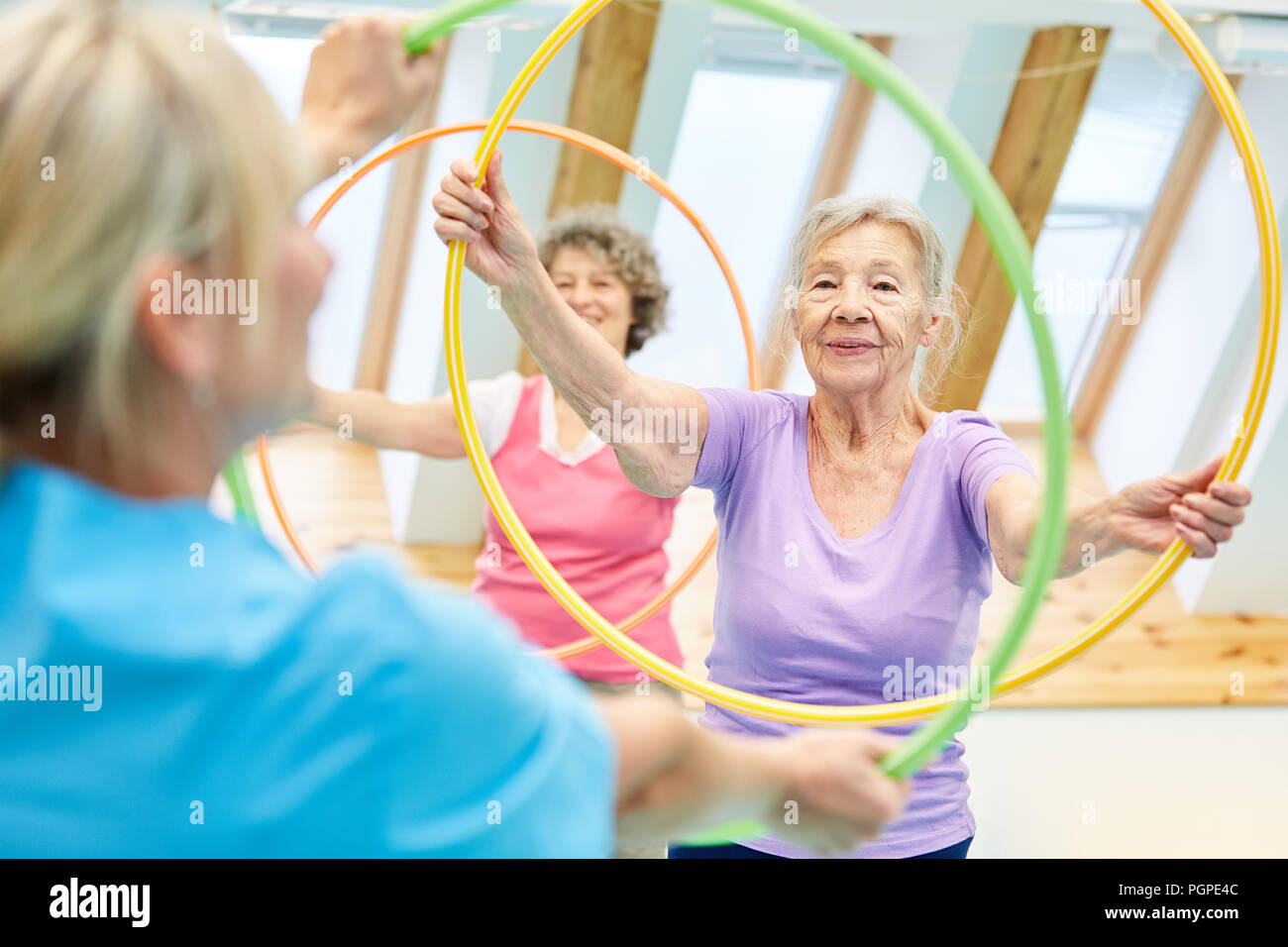 Seniors do fitness training with the tire in the physiotherapy - Stock Image