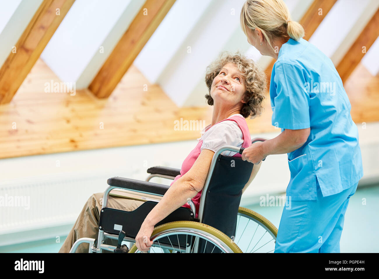 Senior woman as a patient in a wheelchair is being cared for by a caregiver at the rehab clinic - Stock Image