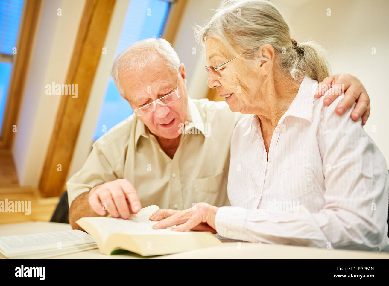 Senior couple with book reading and reading aloud in a nursing home or at home - Stock Image