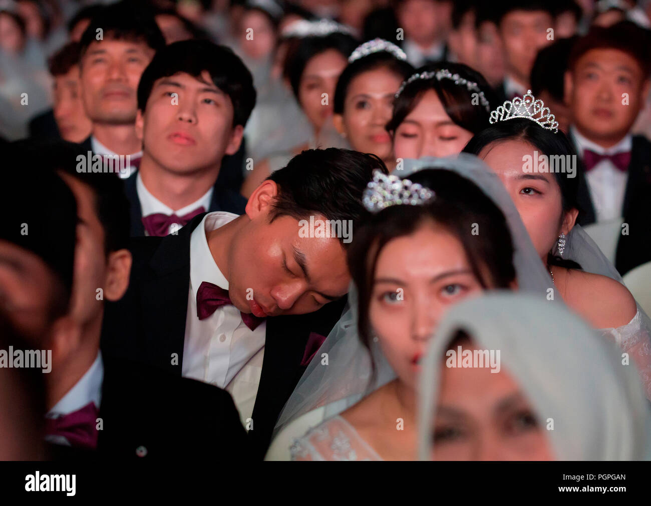 Seoul, South Korea. 27th Aug 2018. Mass wedding ceremony of the Unification Church, Aug 27, 2018 : A bride groom dozes during a mass wedding ceremony of the Unification Church at the CheongShim Peace World Center in Gapyeong, about 60 km (37 miles) northeast of Seoul, South Korea. Four thousand newlywed couples from around the world participated in the mass wedding on Monday, which was organized by Hak Ja Han Moon, wife of the late Reverend Sun Myung Moon. Credit: Aflo Co. Ltd./Alamy Live News - Stock Image