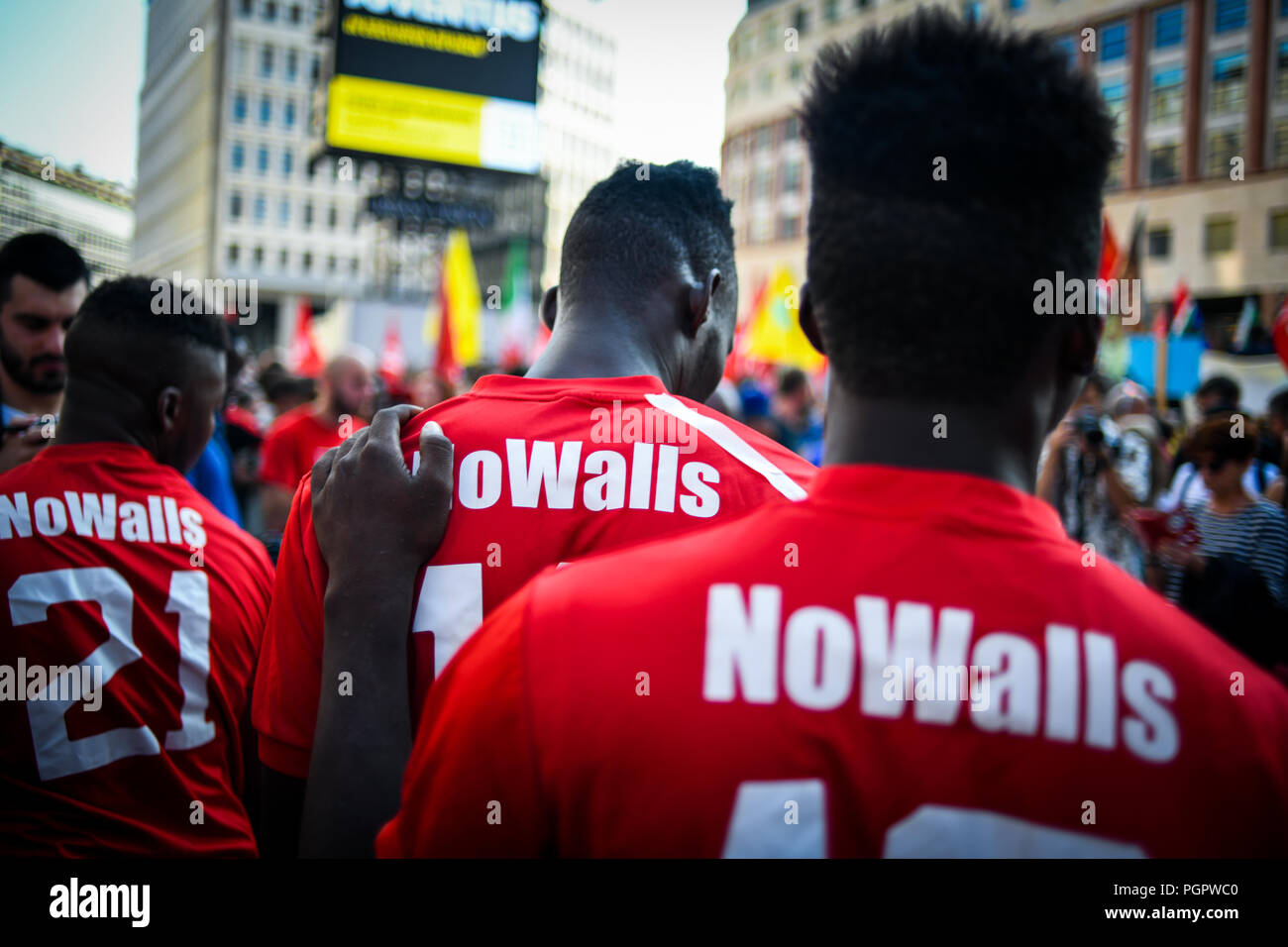 Milan, Italy. 28th Aug 2018. Migrants wearing tshirts reading 'No walls' play football during a protest against the meeting between Prime Minister of Hungary, Viktor Orbán and Italian Interior Minister Matteo Salvini in Milan, Italy on August 28, 2018 Credit: Piero Cruciatti/Alamy Live News - Stock Image